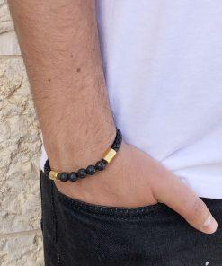 תמונה של דוגמן עם צמיד עור לגבר בצבע שחור וחרוזים בצבע זהב