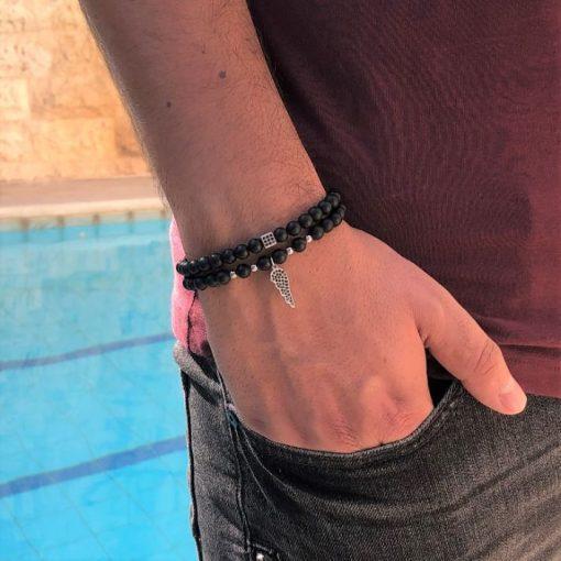 תמונה של דוגמן עם צמידים לגברים בצבע שחור עם תליון נוצה