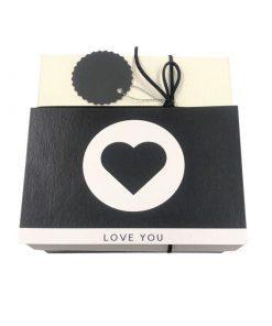 תמונה של קופסת מתנה בצבע שחור לבן עם כרטיס ברכב לב