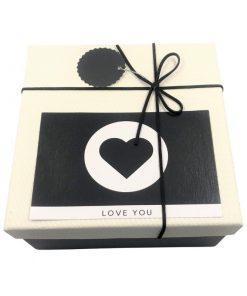 תמונה של קופסת מתנה גדולה בצבע שחור לבן עם כרטיס ברכה